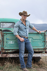 cowboy leaning on a vintage truck in the mountains