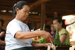 Chan Souck, 55 years old is a member of the Older People's Group. She and younger women help prepare ornaments from natural materials for a wedding ceremony.  These traditional Banana leaf items are used throughout Laos for festivals and religious events.<br /> Had Khen Village, Pakseng District, Luang Prabang Province, Lao PDR