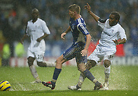 Photo: Aidan Ellis.<br /> Bolton Wanderers v Zenit St Petersburg. UEFA Cup. <br /> 03/11/2005.<br /> Bolton's Jay-Jay Okocha and Zenit's Velice Sumulikoski battle for the ball in th rain
