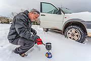 Man heats water for coffee on a portable gas stove in the snow
