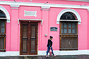 A woman walks past a brightly painted colonial style home in Tlacotalpan, Veracruz, Mexico. The tiny town is painted a riot of colors and features well preserved colonial Caribbean architectural style dating from the mid-16th-century.