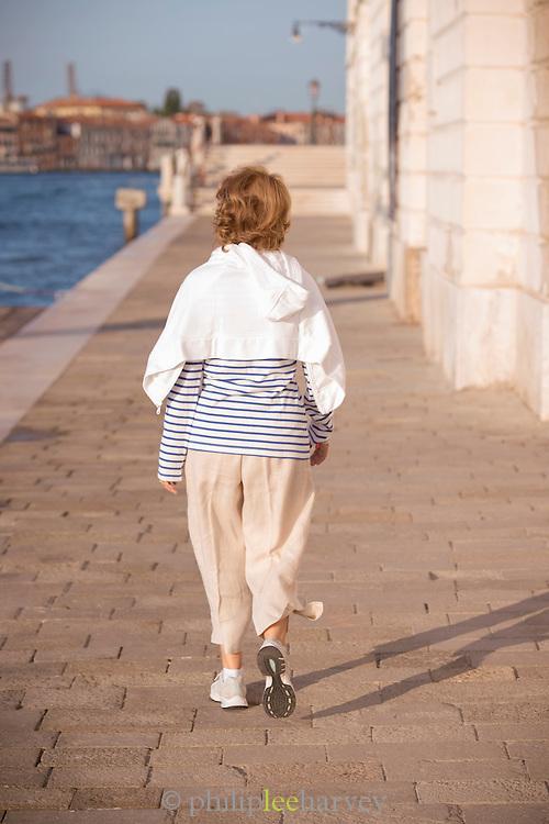 Woman walking along the Fondameta Zattere Ai Saloni. Venice, Italy, Europe