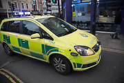 Ambulance rushes by with lights blazing on way to an emergency. London, UK. Small ambulances as part of the emergency services are commonly seen rushing around.