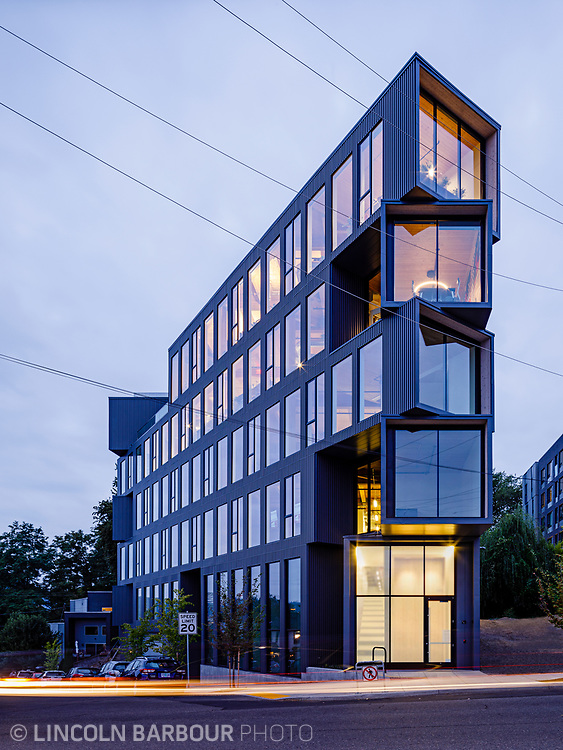 The modernly designed Ironside Building in Portland, Oregon shot at dusk, glowing from the inside.  Car headlights streaking by. Architectural photograph of the Flatiron building designed by Works Progress Architecture