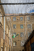 External walls of prison wings of HMP Pentonville, London, UK. The cell windows are protected with metal bars and netting, but green drop lines can be seen hanging off the windows and leading to other cells. This is how prisoners pass contraband items to each other.  The external walls are protected with razor wire. HM Prison Pentonville is an English Category B men's prison, operated by Her Majesty's Prison Service. Pentonville Prison is located on  Caledonian Road in the Barnsbury area of the London Borough of Islington, north London, United Kingdom. (Photo by Andy Aitchison)