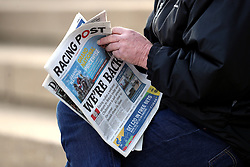 A racegoer reads the Racing Post featuring the front page headline 'We're Back' during the Injured Jockeys Fund Charity Raceday at Plumpton Racecourse.