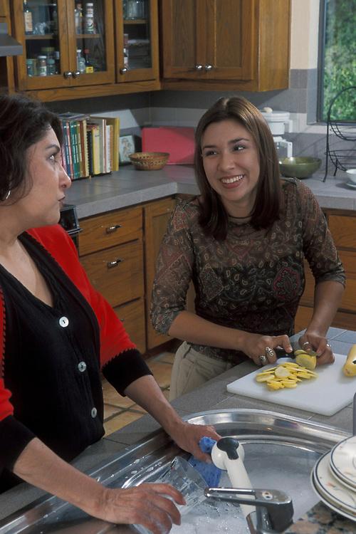 Hispanic mom and daughter prepare food, clean up kitchen.  Model Release.<br /> ©Bob Daemmrich