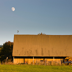 The moon rises over barn at the Clark Farm in Windham, Maine,