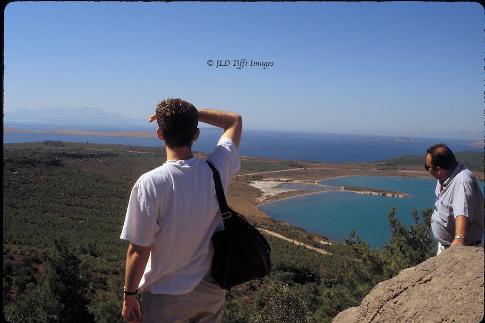 Two men looking toward Island of Lesbos from Ayvalik, Turkey, their viewpoint high over the town.