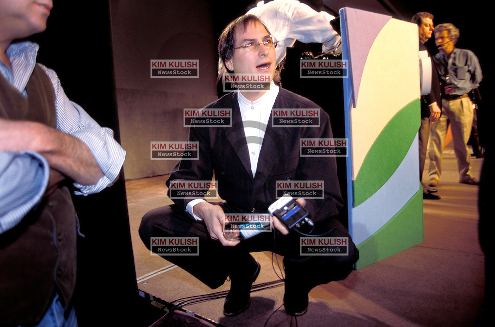 Steve Jobs relaxes at the edge of the stage prior to  speaking  at  Macworld 1997 in San Francisco, California.