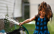 Four-year-old Zaila Egan holds her hair up as she sprays water onto family members as they play in front of their Sherman St. home in South Bend on Tuesday afternoon.