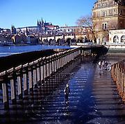 Children ice skating on frozen River Vltava, Prague, Czech Republic