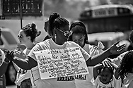 """Stephanie Cooper, the Vice President of Rise St. James  holding a sign in Welcome  Louisaina on the third day of a five day march through Louisiana's 'Cancer Alley' .. The march, held by the Coalition Against Death Alley. The Coalition Against Death Alley (CADA), is a group of Louisiana-based residents and members of various local and state organizations, is calling for a stop to the construction of new petrochemical plants and the passing of stricter regulations on existing industry in the area that include the groups RISE St. James, Justice and Beyond, the Louisiana Bucket Brigade, 350 New Orleans, and the Concerned Citizens of St. John. Louisiana's Cancer Alley, an 80-mile stretch along the Mississippi River, is also known as the """"Petrochemical Corridor,"""" where there are over 100 petrochemical plants and refineries ."""
