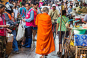 """26 SEPTEMBER 2012 - BANGKOK, THAILAND:  A Buddhist monk walks through the crowd in Khlong Toey Market in Bangkok. Khlong Toey (also called Khlong Toei) Market is one of the largest """"wet markets"""" in Thailand. The market is located in the midst of one of Bangkok's largest slum areas and close to the city's original deep water port. Thousands of people live in the neighboring slum area. Thousands more shop in the sprawling market for fresh fruits and vegetables as well meat, fish and poultry.    PHOTO BY JACK KURTZ"""
