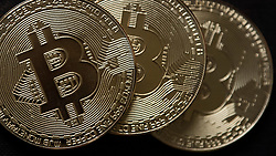 © Licensed to London News Pictures. 11/01/2018. London, UK. A souvenir Bitcoin coin arranged for a photograph. Bitcoin, a cryptocurrency which uses peer-to-peer technology to operate with no central authority, has boomed in price over the last year. Photo credit: Ben Cawthra/LNP