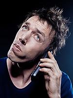 studio portrait on black background of a funny expressive caucasian man phoning strain