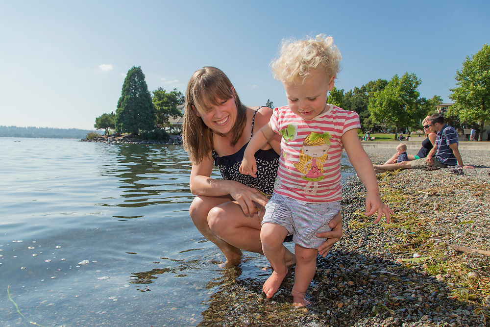 United States, Washington, Kirkland, Mother and baby girl playing at waterfront on Lake Washington