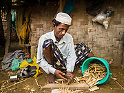 07 NOVEMBER 2014 - SITTWE, RAKHINE, MYANMAR: A Rohingya Muslim man splits sticks to make ice cream bars in front of his hut in an IDP camp for Rohingya. After sectarian violence devastated Rohingya communities and left hundreds of Rohingya dead in 2012, the government of Myanmar forced more than 140,000 Rohingya Muslims who used to live in and around Sittwe, Myanmar, into squalid Internal Displaced Persons camps. The government says the Rohingya are not Burmese citizens, that they are illegal immigrants from Bangladesh. The Bangladesh government says the Rohingya are Burmese and the Rohingya insist that they have lived in Burma for generations. The camps are about 20 minutes from Sittwe but the Rohingya who live in the camps are not allowed to leave without government permission. They are not allowed to work outside the camps, they are not allowed to go to Sittwe to use the hospital, go to school or do business. The camps have no electricity. Water is delivered through community wells. There are small schools funded by NOGs in the camps and a few private clinics but medical care is costly and not reliable.   PHOTO BY JACK KURTZ