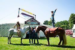 """Giffords Circus presents """"Xanadu"""" <br /> Produced by Nell Gifford  - Directed by Cal McCrystal<br /> At Chisiwck House and Park, London, Great Britain <br /> Press view <br /> 27th June 2019 <br /> <br /> 7th and 8th generation horse-people The Donnert Family from hungry performing in the UK for the first time at Giffords Circus<br /> <br /> The famous Clown Tweedy performing at Giffords Circus <br /> <br /> Roll up, roll in to the stately pleasure-dome for miracles, song, symphony and enchantment. Musicians, horses, clowns and tumblers enfolded in this joyful paradise, with music loud and long - the Giffords Circus caravan will be taking to the road for a 2019 summer of love.<br /> <br /> <br /> It is midsummer 1973 in Hyde Park and the flower power movement is at its height. Hippies, hipsters, rock stars, musicians, wild women and global nomads with Shamanic horses gather to play, sing, dance, protest and perform. Policemen and a family of out-of-towners get caught up in the celebrations. Will they get in the groove? Nell Gifford builds a pleasure dome and Tweedy has a job in the kitchen as he thought everyone was talking about """"Flour Power"""". As evening approaches, the ever more chaotic event careers towards a joyful, transcendental finale. <br /> <br /> Photograph by Elliott Franks"""