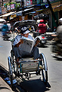 A cyclo driver catches up on the news while waiting for passengers. Cyclos were once popular and often driver by former South Vietnamese Army members who were shunned from other work. But today, with motorbikes and taxis they are becoming more rare. Robert Dodge, a Washington DC photographer and writer, has been working on his Vietnam 40 Years Later project since 2005. The project has taken him throughout Vietnam, including Hanoi, Ho Chi Minh City (Saigon), Nha Trang, Mue Nie, Phan Thiet, the Mekong, Sapa, Ninh Binh and the Perfume Pagoda. His images capture scenes and people from women in conical hats planting rice along the Red River in the north to men and women working in the floating markets on the Mekong River and its tributaries. Robert's project also captures the traditions of ancient Asia in the rural markets, Buddhist Monasteries and the celebrations around Tet, the Lunar New Year. Also to be found are images of the emerging modern Vietnam, such as young people eating and drinking and embracing the fashions and music of the West. His book. Vietnam 40 Years Later, was published March 2014 by Damiani Editore of Italy.
