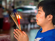 """10 AUGUST 2014 - BANGKOK, THAILAND: A man prays on the first day of Ghost Month at the Poh Teck Tung Shrine in Bangkok. The seventh month of the Chinese Lunar calendar is called """"Ghost Month"""" during which ghosts and spirits, including those of the deceased ancestors, come out from the lower realm. It is common for Chinese people to make merit during the month by burning """"hell money"""" and presenting food to the ghosts.     PHOTO BY JACK KURTZ"""