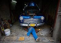 cuban mechanic working on chevy in cuban auto shop