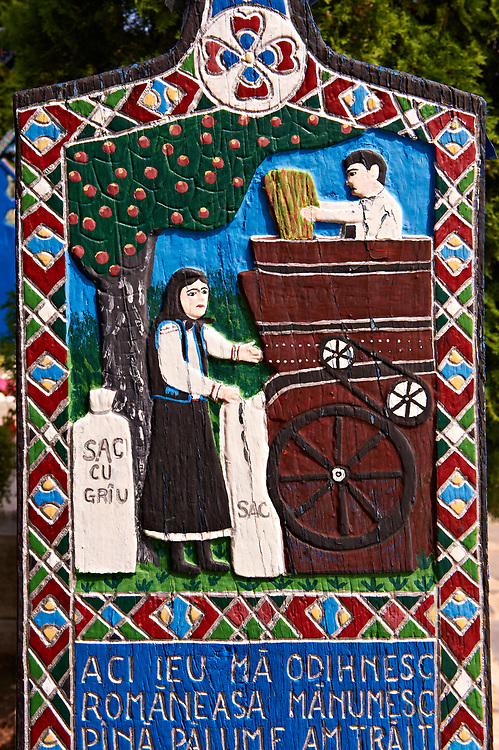 Tombstone of a thresher showing a couple threshing wheat,   The  Merry Cemetery ( Cimitirul Vesel ),  Săpânţa, Maramares, Northern Transylvania, Romania.  The naive folk art style of the tombstones created by woodcarver  Stan Ioan Pătraş (1909 - 1977) who created in his lifetime over 700 colourfully painted wooden tombstones with small relief portrait carvings of the deceased or with scenes depicting them at work or play or surprisingly showing the violent accident that killed them. Each tombstone has an inscription about the person, sometimes a light hearted  limerick in Romanian. .<br /> <br /> Visit our ROMANIA HISTORIC PLACXES PHOTO COLLECTIONS for more photos to download or buy as wall art prints https://funkystock.photoshelter.com/gallery-collection/Pictures-Images-of-Romania-Photos-of-Romanian-Historic-Landmark-Sites/C00001TITiQwAdS8