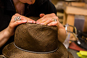 Shaping the crease on the crown of a straw fedora. Once the shape has been established, a wooden block called a tipper will be tied in place to hold the crease.