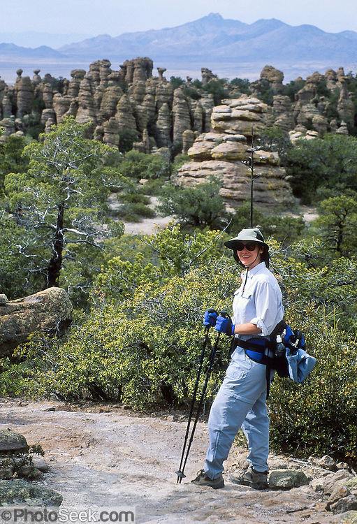 A hiker admires hoodoos at Chiricahua National Monument, Arizona, USA. The Heart of the Rocks Loop Trail (7 to 9 miles) makes an excellent day hike through fascinating arrays of hoodoos. 27 million years ago, huge volcanic eruptions laid down 2000 feet of ash and pumice which fused into rhyolitic tuff. This rock has eroded into fascinating hoodoos, spires, and balanced rocks which lie above the surrounding desert grasslands at elevations between 5100 and 7800 feet. At Chiricahua, the Sonoran desert meets the Chihuahuan desert, and the Rocky Mountains meet Mexico's Sierra Madre, making one of the most biologically diverse areas in the northern hemisphere. While we drove the dirt road to nearby Portal, Arizona, Carol saw a mountain lion crossing the road! Other animals here include javelina, coatimundi, bears, skunks, and deer. For licensing options, please inquire.