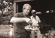 President Carter samples a watermelon as he visits with tenant farmer Leonard Wright who works the Carter farmland.