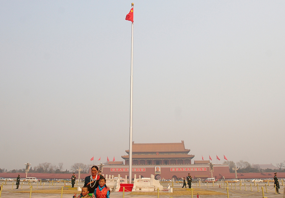A family of tourists from western China pose at Tiananmen Square with the south entrance to the Forbidden City behind them in Beijing, China.