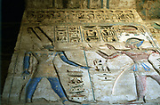 Amon-Ra, Egyptian god, (left) and Rameses III (1198-1167 BC) second king of 20th dynasty. Painted relief, temple of Rameses II, Medinet Habu. Ankh held by Amon-Ra. Empty Eye of Horus bottom centre.