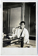 male person relaxing and drinking sake in hotel room 1950s