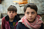 """L Abdulazeen 12,  R Abdulga, 14. Kilis, near Syrian - Turkish border, Abdulazeen and Abdulga, are members of a refugee family from Aleppo and live each in a tiny, wet and cold storage room. It has been two months they are here. Ahmad (40 years), the father, worked in a factory in Aleppo. He has 4 boys and 3 girls. He is looking for work in Turkey since 1,5 months. The monthly rent is 200 dollar, they don't have any money left. They say they will return to Aleppo in 3-5 days. Abdulga - 14 said: """"I'm afraid of the bombs, me and my brothers, there has been bomb attacks, we saw the body of a dead person, we were full of fear, our stomach ached. It was in Bab Alwa, I went out to by fruit and bread and we saw the barrel bomb fall. I don't go to school since 3 years."""""""