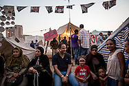A family sits in the centre of Tahrir Square, home to Egypt's anti-Morsi movement, made infamous since the revolution against Mubarak in 2011