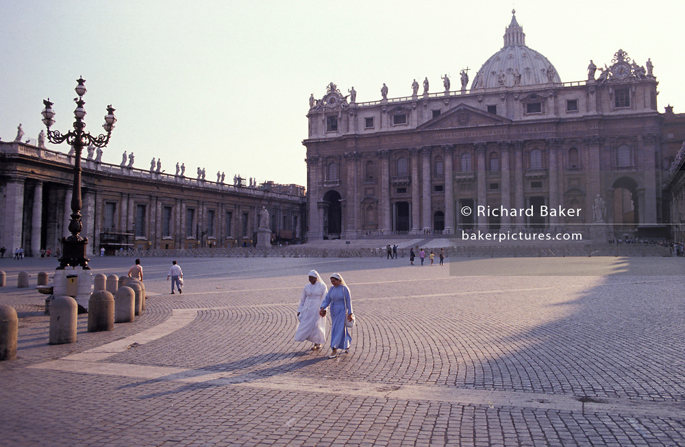 Two nuns with their early morning shadows, walk over the cobbles of St. Peter's Square in front of the Vatican, on 3rd November 1999, in Rome, Italy.