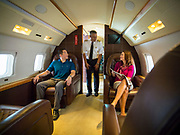 A male model serving as the Captain of this corporate jet greets his passengers.  Advertising commissioned for Phillips 66 Aviation Fuels.<br />