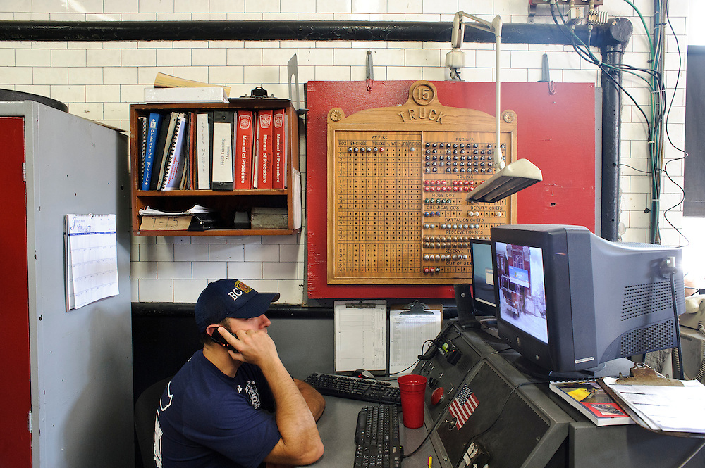 (photo by Matt Roth).Assignment ID: 30127696A.Wednesday, June 20, 2012..Baltimore Truck Company 15 FF/PM Will Thomas answers the phone at while on duty at the 104 year old station. Due to a $48 million budget fall, as of July 1st, all the members of Truck Company 15 are slated to be disbanded and reassigned to other companies and their truck will be used as a reserve truck. ..City Councilman William Pete Welch proposes advertisements be allowed on Baltimore City Fire Department vehicles as a way to combat a $48 million budget shortfall, rather than disbanding three companies, including Truck Company 15, which services East Baltimore.