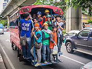 "07 OCTOBER 2012 - BANGKOK, THAILAND: Construction workers crowd into the back of a ""songthaew"" as they leave a job site at an international hotel on Sukhumvit Road in Bangkok. A songthaew is a pickup truck converted to a bus or shared taxi by the installation of two bench seats in the back. They are commonly used in rural areas and as company provided transport in Malaysia, Thailand and Laos.     PHOTO BY JACK KURTZ"