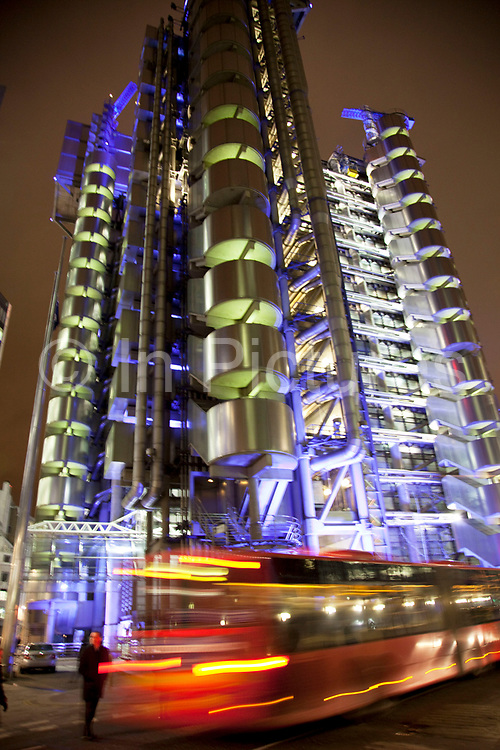 Night time scene in the City of London. The Lloyds building lit up with laverdar / blue coloured lights (also sometimes known as the Inside-Out Building) is the home of the insurance institution Lloyd's of London, and is located at 1, Lime Street. It was designed by architect Richard Rogers and built between 1978 and 1986. The building was innovative in having its services such as staircases, lifts, electrical power conduits and water pipes on the outside, leaving an uncluttered space inside.