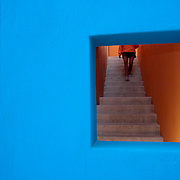 A person walking downstairs is seen through a window of a building.  Mexico.