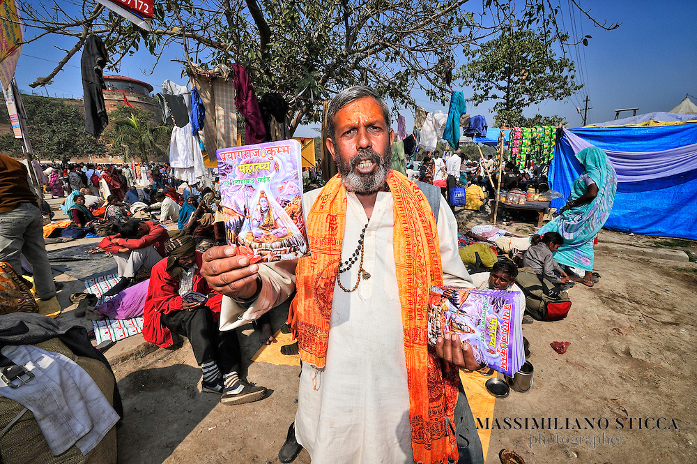 A man  in Allahabad sells a prayer book for other pilgrims.