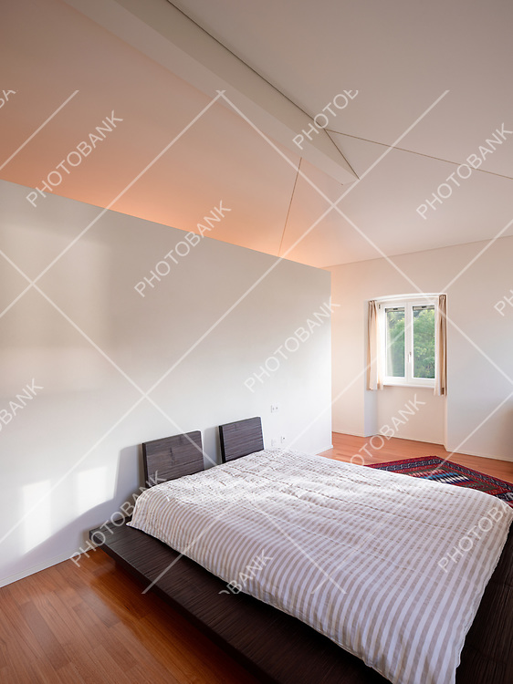 Interior of a minimal bedroom, with only one bed and a beam of light entering. The floor is made of wood and the bed is low, Japanese style.