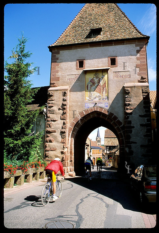 Cyclists race through arch of city gate on a summer morning in the town of Boersch, Alsace. France