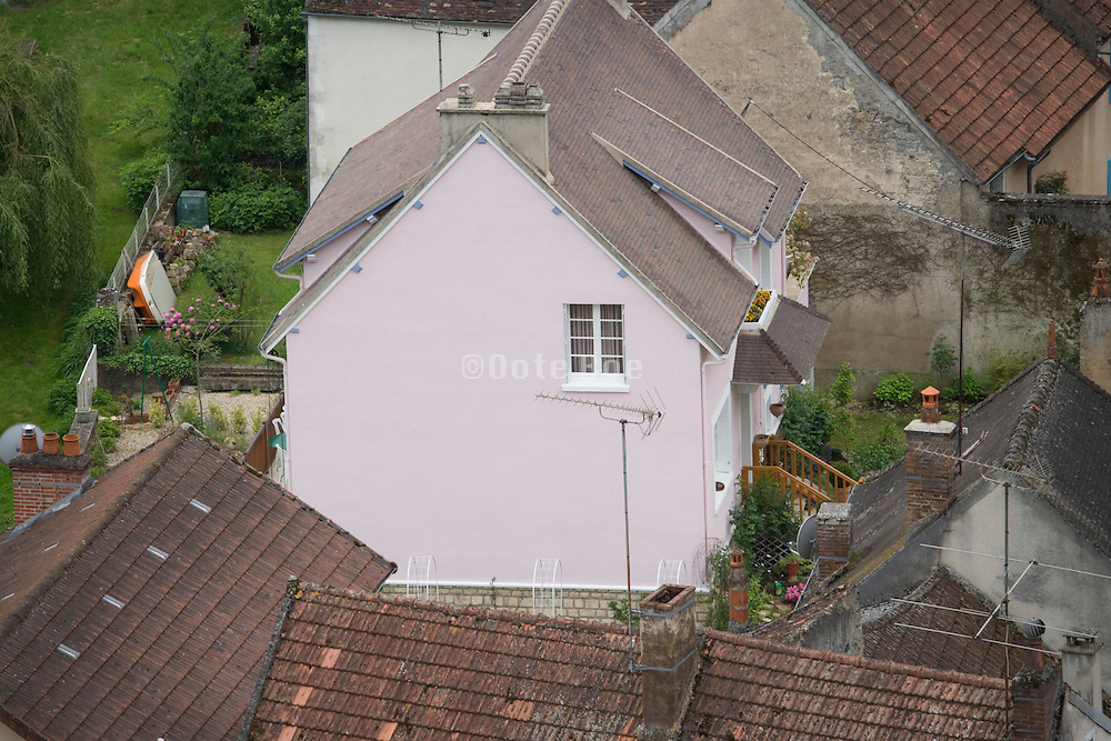 a pink painted house in a little village France