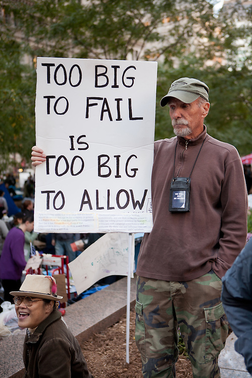 "A man holds a sign reading ""Too big to fail is too big to allow"""