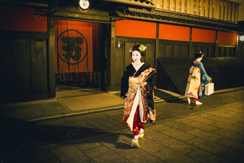 Maikos walking in Gion.Gion is an old district of Kyoto with old houses called machilla many of the tea houses and restaurants famous because it is were many Geishas ,called Geikos in  this city, perform every night. For the well conserved architecture the presence of geikos and maikos and the abundance of entertainment it is also one of the main tourist attractions of the city. At the beginning of the century more than 80000 lived in Japan and 800 of those in Gion, nowadays it is believed that this number is less than 1500 all over the country.Around 200 geikos and around 70 maikos  live in Kyoto. In spite of this decline thye last years have seen a resurgence of girls wanting to access this ancient profession that now not only entertains men but also other women families and foreigners that want to take a glimpse in the misterious world of the Geishas.