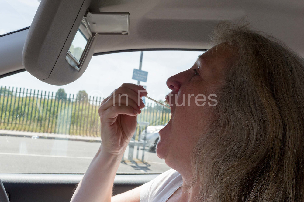 A middle-aged lady inserts a swab into her mouth to reach her tonsils from the drivers seat of her car during a self-administered Coronavirus COVID-19 test in south London. There are four steps to the self-administered Covid-19 test inserting a swab into the nose and throat which the public works through in their car, windows up and all communications with army personnel via phone, in a south London leisure centre, on 2nd June 2020, in London, England. The kit provided consists of a booklet, plastic bag, swab, vial, bar codes and a sealable biohazard bag. The swab sample is taken from the back of the throat and nasal passage with the contents sealed and returned to soldiers through a narrow window. The whole process takes between 5-10mins with results available within 48hrs.