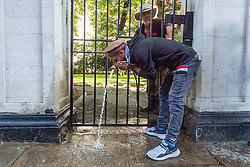 © Licensed to London News Pictures. 07/09/2021. London, UK. A pro Afghanistan demonstrator protesting outside the Pakistan High Commission take cold hose pipe water from a gardener to cool off from the 29C mini heatwave hot weather. Photo credit: Ray Tang/LNP