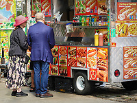 Tourists waiting for their snack at a food cart on Fifth Avenue
